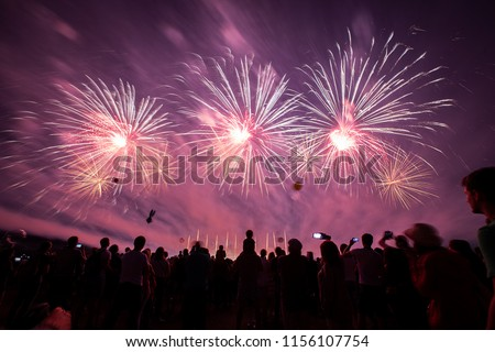 a crowd of people came to the festival, a festival of fireworks, explosions of pyrotechnic charges, volleys of salutes against the backdrop of happy people rejoicing in the beautiful spectacle, multic Stock photo ©