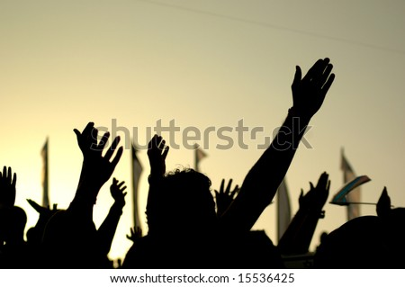 A crowd of people in silhouette raises their hands against the background of a yellow sunset.