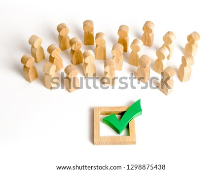 A crowd of people looks at a green check mark. Voting and election concept. Referendum, revolution. Forcible overthrow. Making the right decision, majority agreement. Peace and order, legitimization.