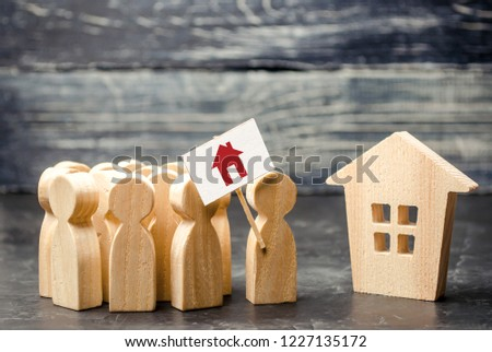 A crowd of people with a poster standing near the house. The concept of finding housing, a new home. High demand for housing, affordable loans and mortgages. Refugees seek asylum. meeting place
