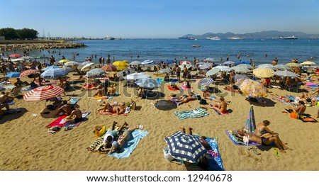 A crowd of vacationers enjoy the warm beaches of Cannes, France during the summer
