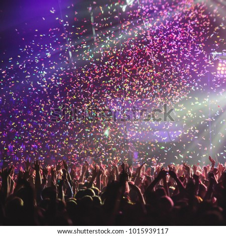 A crowded concert hall with scene stage lights, rock show performance, with people silhouette #1015939117