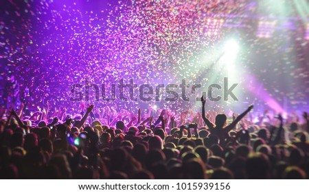 A crowded concert hall with scene stage lights, rock show performance, with people silhouette #1015939156