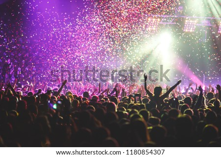 A crowded concert hall with scene stage lights, rock show performance, with people silhouette  #1180854307