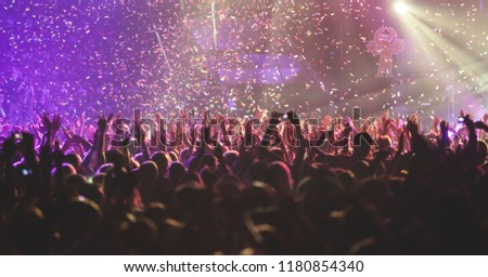 A crowded concert hall with scene stage lights, rock show performance, with people silhouette  #1180854340