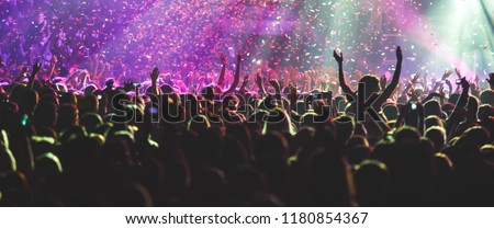 A crowded concert hall with scene stage lights, rock show performance, with people silhouette  #1180854367