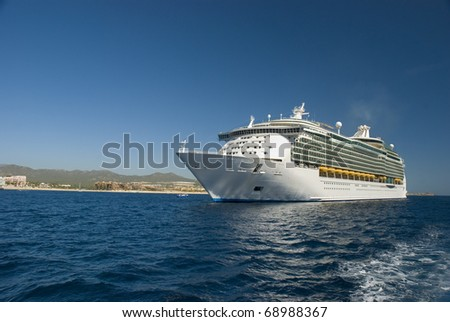 A Cruise ship docked in Cabo San Lucas, Mexico. The beach and condominiums are in the background.
