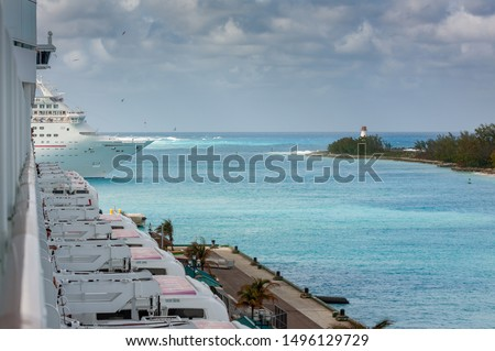 A cruise ship turns starboard into Nassau Harbor. The Nassau Harbor Lighthouse is in the background, and another cruise ship is in the foreground, anchored at Prince George Wharf. #1496129729