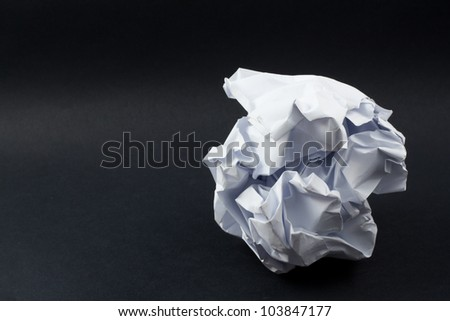 A crumpled paper ball in a black background - stock photo