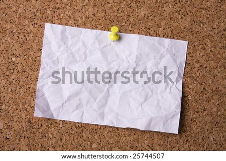 A crumpled paper stuck to a cork noticeboard