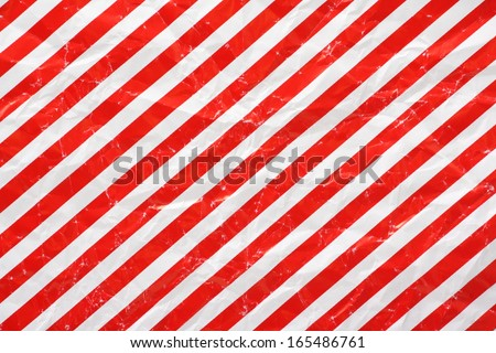 A crumpled sheet of Christmas wrapping paper in a red and white stripe pattern for use as a background