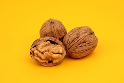 a crushed walnut and two whole walnuts on a yellow background