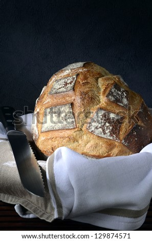 a crusty french pain de campagne wrapped with a white napkin with a serrated bread knife.