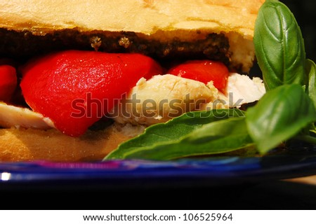 A crusty roll spread with basil pesto and filled with chicken breast and roasted red peppers - stock photo