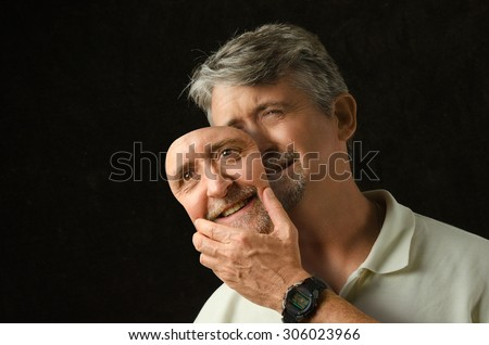 Stock Photo A crying depressed bipolar disorder man is trying to hide his tears with a fake smile happiness mask that looks exactly like his face.