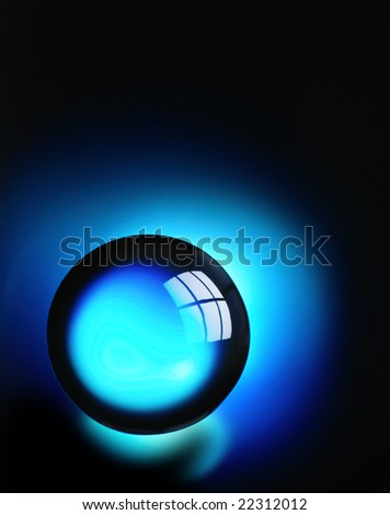 A crystal ball on a blue background with window reflection