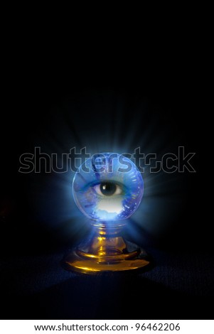 A crystal ball on black with a blueish glow and an eye peering out at you.