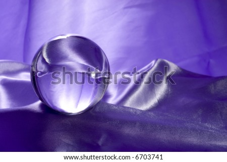 A Crystal Ball on Purple Fabric. - stock photo