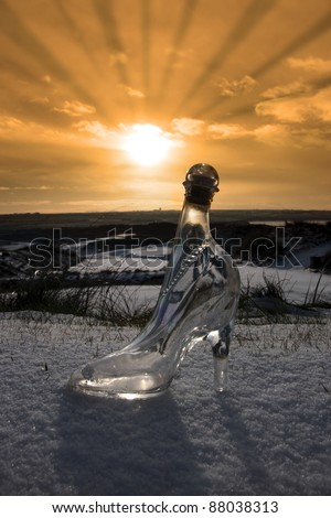 a crystal glass slipper in a snow covered irish golf course at sunset for a concept on ladies golf