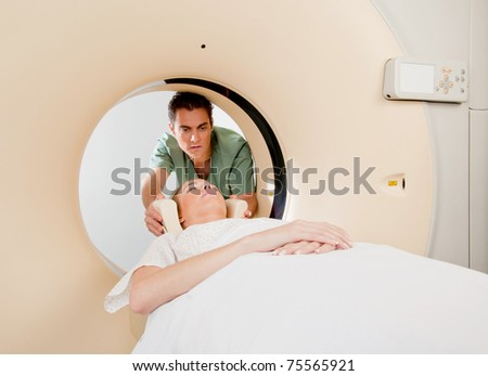 A CT scan technician aligning a patient in the machine