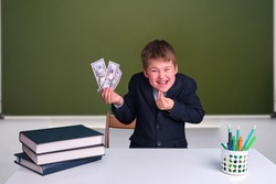 A cunning boy with money in his hands at a desk in a school classroom. US dollars in junior's hand on a blackboard background, copy space for text