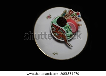 A cup cake on white dish with decorated on topping and whipping cream in the them of happy birthday on black background and top view.Family time and happiness concept.