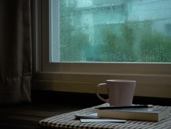 a cup coffee and book  on rainy day window background