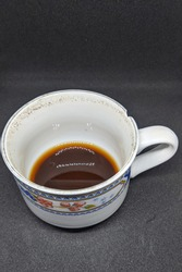 A cup filled with coffee that has been drunk,  An empty cup,  Dirty cups isolated on black background