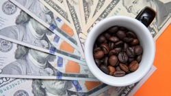 a cup full of coffee beans stands on dollar bills. Concept showing the rise or fall of coffee prices in the markets.