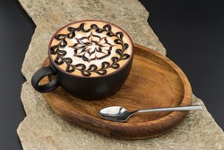 a cup of a cappucino with a nice pattern served on a wooden server with tea spoon