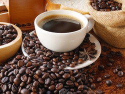 A cup of aroma hot coffee in white cup for drink in this morning with coffee powder and coffee beans in sack and coffee beans in wooden bowl and some breads