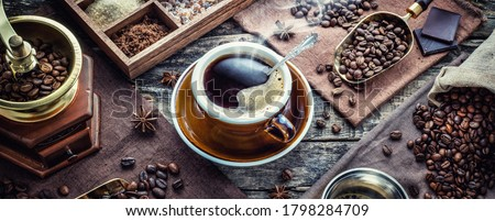 A cup of aromatic black coffee, a coffee grinder, a coffee maker, beans of different varieties on the table. Morning espresso or Americano coffee for breakfast in a beautiful brown cup.