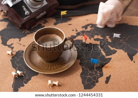 A cup of aromatic coffee on the map and accessories for travel. Vintage photo. Tourism and holidays. Free space for text. Top view #1244454331