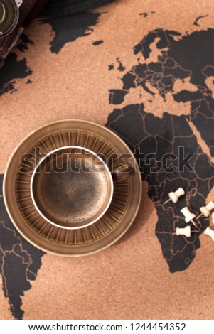 A cup of aromatic coffee on the map and accessories for travel. Vintage photo. Tourism and holidays. Free space for text. Top view #1244454352