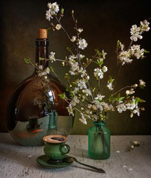 A cup of aromatic coffee on the table and a spring bouquet. A large bottle in which flowers and a cup are reflected. Still life. Vintage.