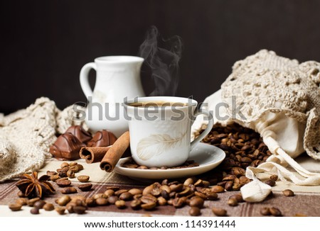 A cup of aromatic hot coffee, coffee beans, milk jug & cinnamon