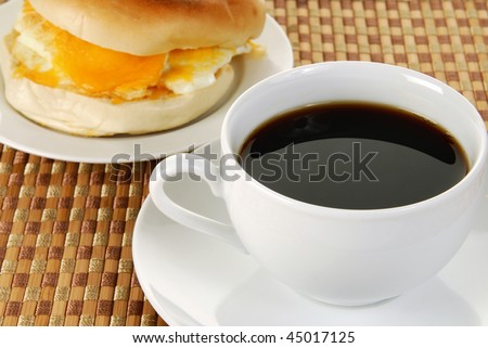 A cup of black coffee and a bagel and egg sandwich