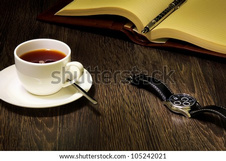 A cup of black coffee and a book