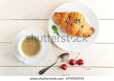 A cup of black coffee and a plate with a croissant. View from above. The croissant is decorated with chocolate crumbs. On a plate of mint leaves. Complement the composition of a teaspoon and cherry.