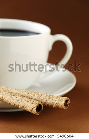 a cup of black coffee and chocolate cream wafers. Focus is on wafers.