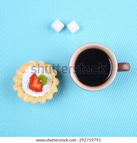 A cup of black coffee, sugar cubes and cake. Strawberry cake with cream. Dessert tart. Cream cake with strawberries and mint leaves. Breakfast, lunch. Cafeteria and restaurant. Food and sweets.