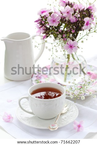 A cup of black tea  and phlox in vase