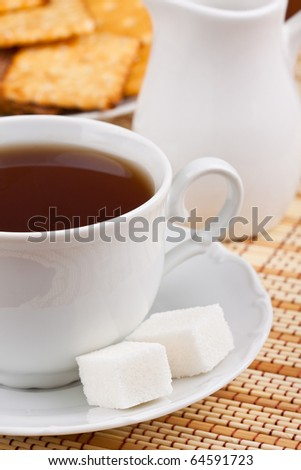 A cup of black tea with a lump sugar and crackers for breakfast