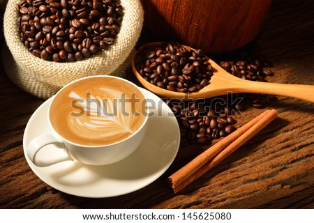 A cup of cafe latte and coffee beans