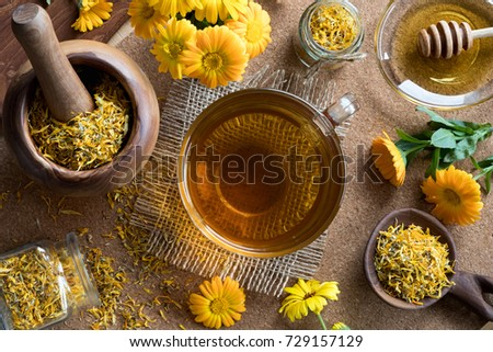 A cup of calendula (marigold) tea on a table, with fresh and dry calendula flowers in the background