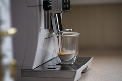 a cup of cappuccino and a coffee machine in the morning