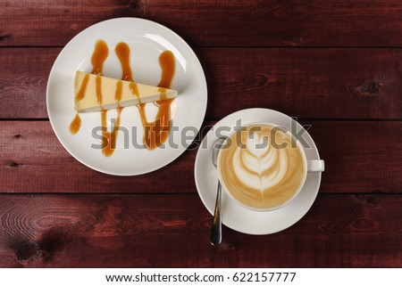 A cup of cappuccino and a piece of cheesecake, drizzled in caramel sauce are in white dish on wooden maroon table. The view from the top