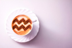 a cup of cappuccino coffee with a pattern of the aquarius aquarius zodiac sign on milk foam