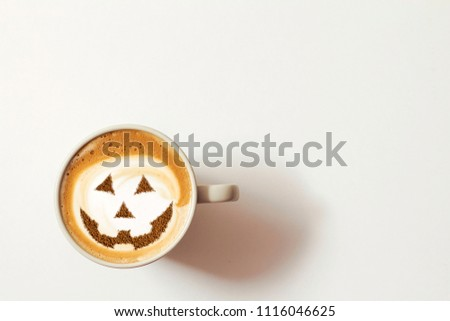 a cup of cappuccino coffee with a picture of a halloween symbol from cinnamon on milk foam