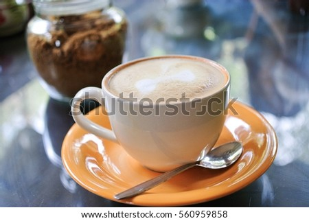 a cup of cappuccino in orange saucer #560959858